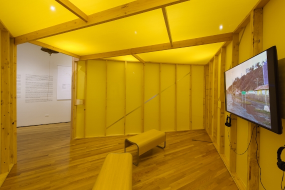 Pablo Helguera. The School of Panamerican Unrest, 2006; installation view inside makeshift schoolhouse, The Schoolhouse and the Bus, 2017. Courtesy of AD&A Museum. [image description: view of interior of yellow schoolhouse, on left is exit with white wall in background, on the right is a monitor playing footage of a landscape]