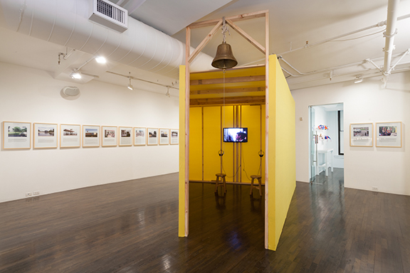 Pablo Helguera, The School of Panamerican Unrest, 2006. Installation shot at The 8th Floor. Courtesy of the artist. [image description: framed images and texts run along the left wall, in the center, is a schoolhouse made of yellow plastic coating and a wooden structure inside, it has a school bell in the front of it]
