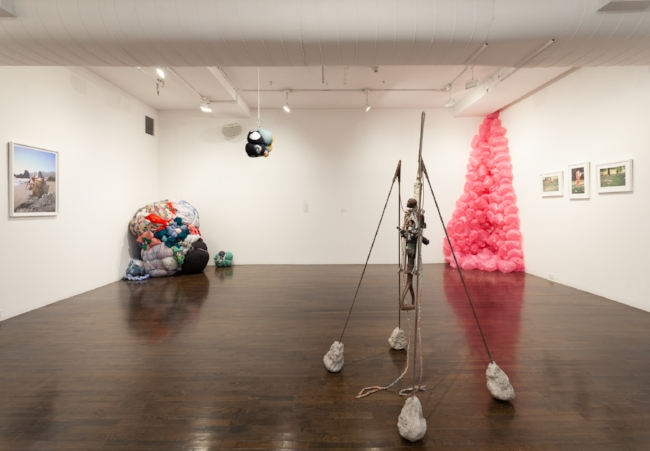 Installation view featuring (left to right) Shinique Smith, Roberto Visani and Maren Hassinger. [image description: installation shot of numerous sculptures and photographs, on the left are multicolored bundles of clothes bound with rope, on the right is a large floor to ceiling sculpture made from pink inflated plastic bags, in the foreground is a human figure supported by iron rods]
