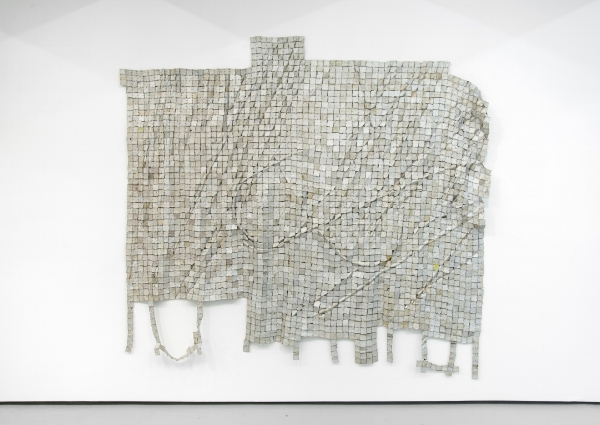 El Anatsui,  Metas II , 2014. Found aluminum and copper wire. ©El Anatsui. Courtesy of the artist and Jack Shainman Gallery, New York. [image description: geometric large gray shape on white wall, it is made from small squares of aluminum with an abstract configuration]