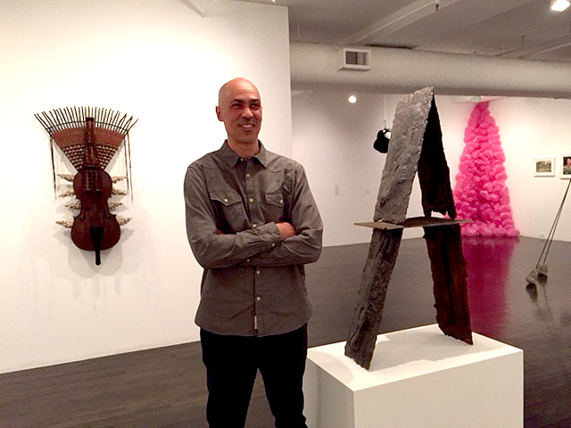 Roberto Visani with his cast iron sculpture  Patterson Stack , 2016, at The 8th Floor. [image description: artist stands with arms folded in gray shirt to the left of his sculpture on the right, sculpture is made from stacked metal casts of the molds from guns, in a house of cards style structure]