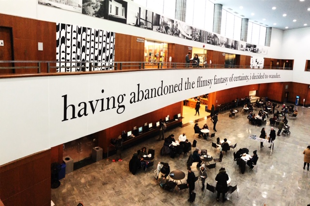 """Kameelah Janan Rasheed, Scoring the Stacks , 2019. Installation at Brooklyn Public Library.  Photograph courtesy of the artist. [image description: photograph taken in Brooklyn Library from second floor depicting the opposite balcony, where text printed on the balcony walkway says """"having abandoned the flimsy fantasy of certainty, i decided to wander""""]"""