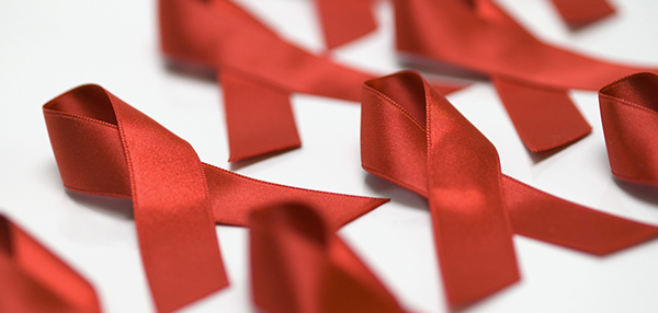 [image description: red looped ribbons, the symbol of the AIDS movement, lined up in two lines diagonally against a white background]