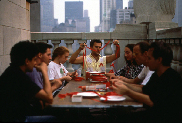 Red Ribbon-making workshop (1991). Courtesy of Visual AIDS. [photograph of people making AIDS ribbons, three people are on either side of the table, man in the middle holds up strings of ribbon]