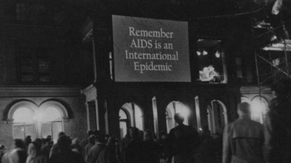 Electric Blanket (1990). Courtesy of Visual AIDS. [black and white photograph of exterior of building with the text 'Remember Aids is an International Epidemic' projected on the front of it, people look on in the foreground]