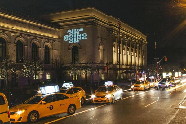 """Kay Rosen's """"AIDS ON GOING GOING ON"""" (2013) projected on the Metropolitan Museum by The Illuminator for RADIANT PRESENCE, Day With(out) Art 2015. Courtesy of Visual AIDS/Elliot Luscombe (lvscombe.com. [color photograph of exterior of museum at night, 'AIDS On Going Going On' is projected onto the side wall, NY taxis go by the building in the foreground]"""