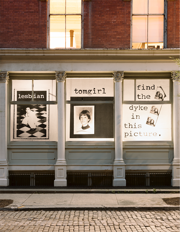 """[image description: exterior of the Leslie-Lohman Museum, all of the windows on the ground floor are covered in artwork. the art in the windows is of different portraits of the members of Fierce Pussy as children overlayed with different pejorative texts or phrases, in this case """"find the dyke in this picture""""]"""