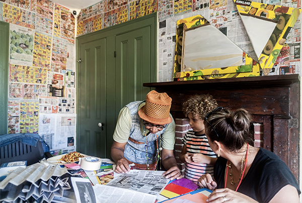 Artist Xenobia Bailey conducting workshop at Weeksville Heritage Center. [image description: photograph of Bailey on left with an orange hat, with a child and another woman on the right, they stand in the artist's installation at the Hunterfly Road Historic Houses, where she has covered the walls in vibrant newsprint and patterns in yellow, and orange]