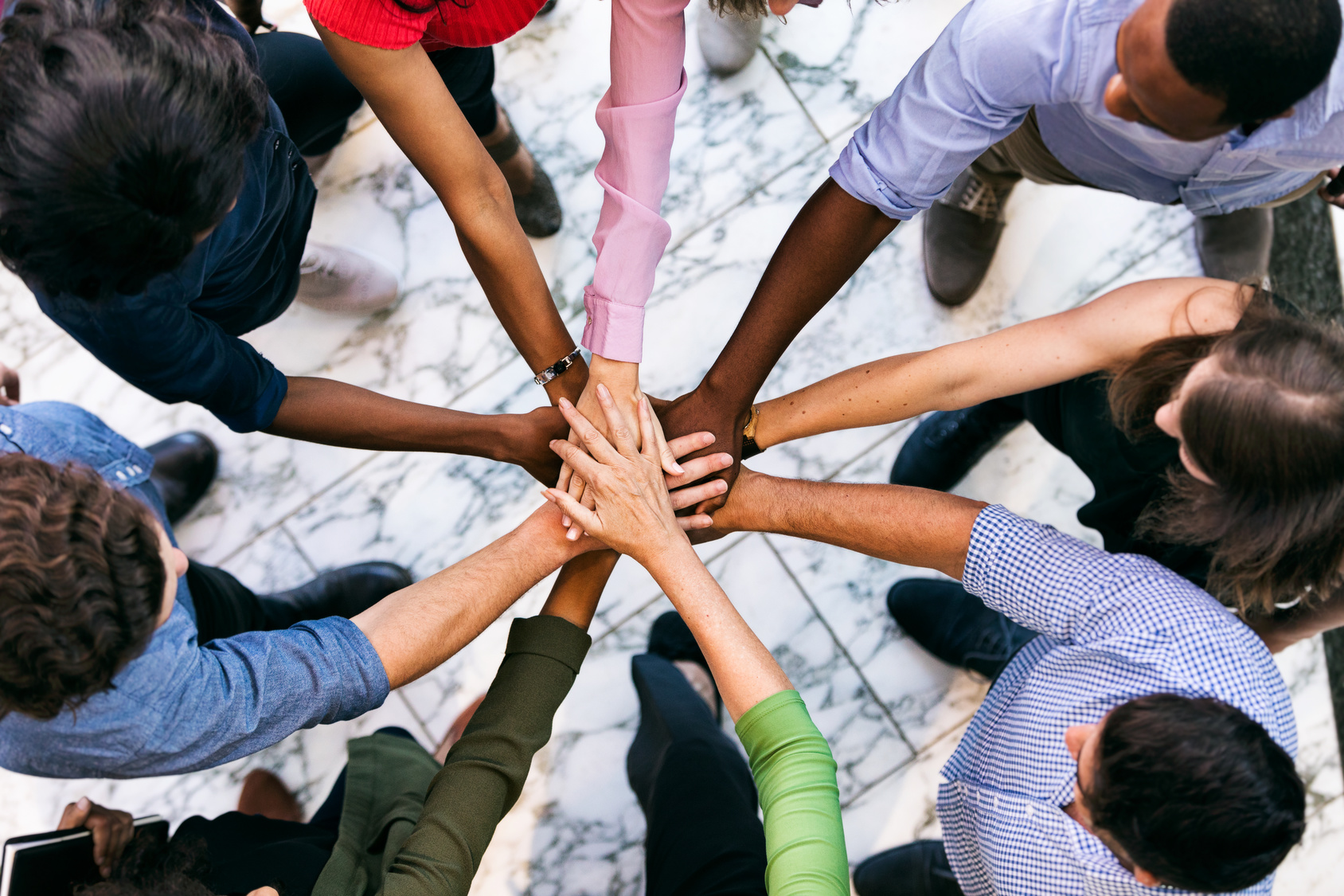 Workspace: Team Of Diverse Workers Put Hands Together