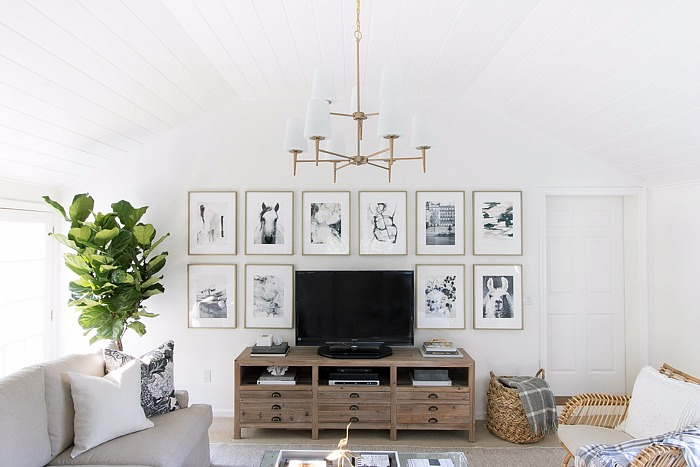 Family-room-with-art-wall-surrounding-TV-two-tiered-chandelier-neutral-sectional-rattan-accent-chair-and-acrylic-coffee-table.jpg