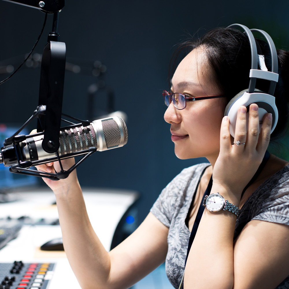 Since 1982 Artsmarketing Services has been working with Public Broadcasters all across North America to build audiences, secure donations, identify planned gifts and build endowment and capital campaigns. Image of woman in a recording studio at mic with headphones.