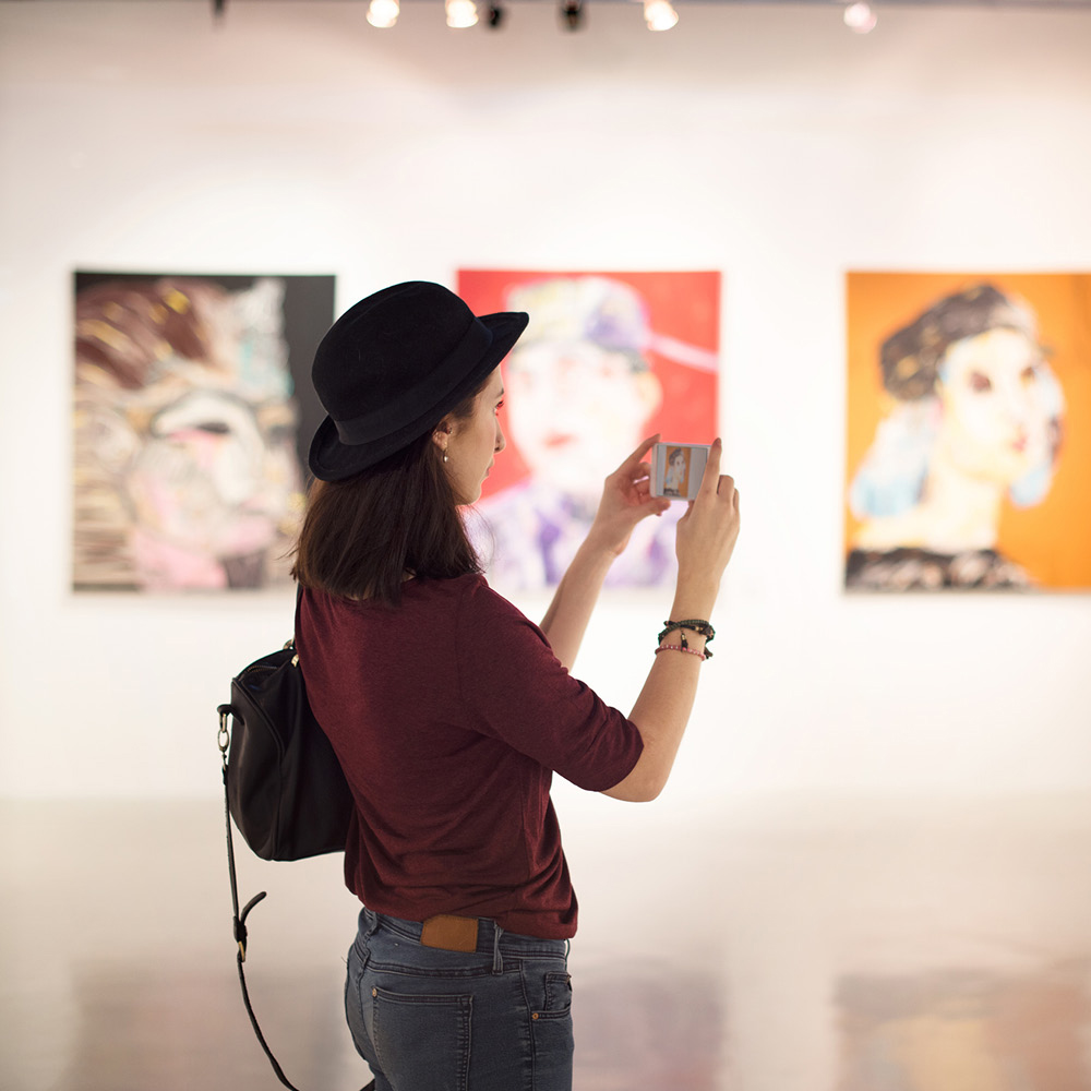 Artsmarketing Services works with museums, zoos, aquariums and cultural institutions across North America to increase retention of members and reactivation of lapsed members. Image of woman taking a picture at an art exhibit.