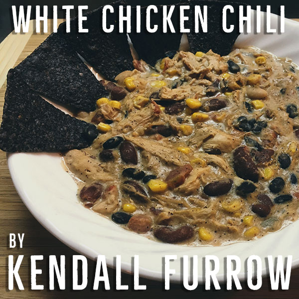 """""""Imagine a brisk autumn morning tailgate; Frosty grass, visible breath and toboggan hats all around. Now imagine holding a steamy bowl of warm, spicy white chicken chili served with fresh tortilla chips in lieu of that old kitchen spoon. A bowl of this spicy goodness will make stomachs happy, full and warm all around just in time for the first kickoff of the day."""""""