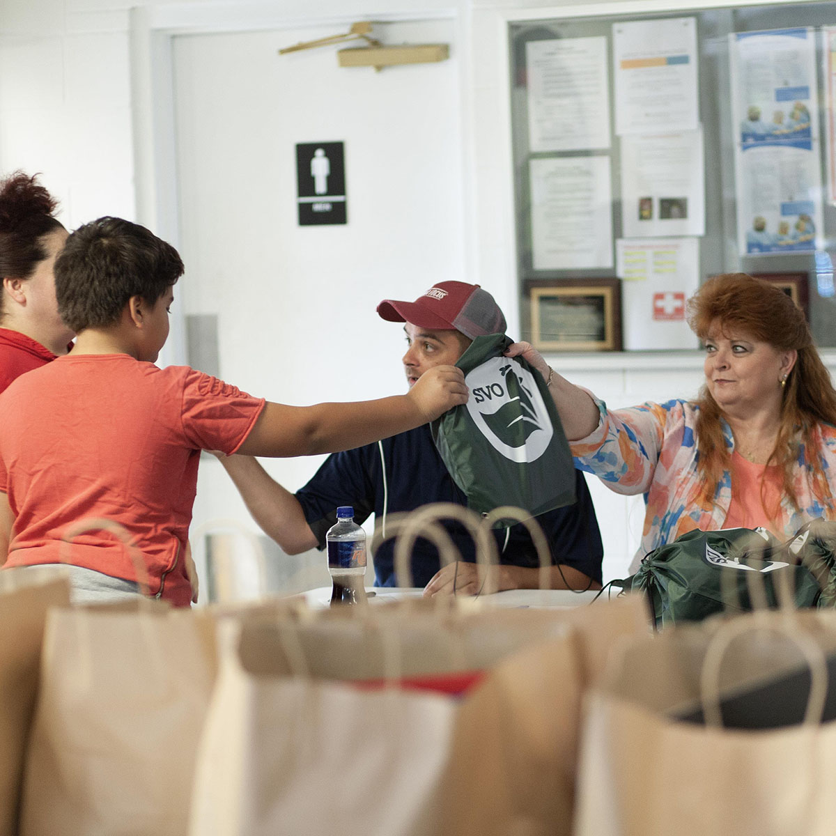 Mike Breeden and Terry Coffman hand supply bags to families