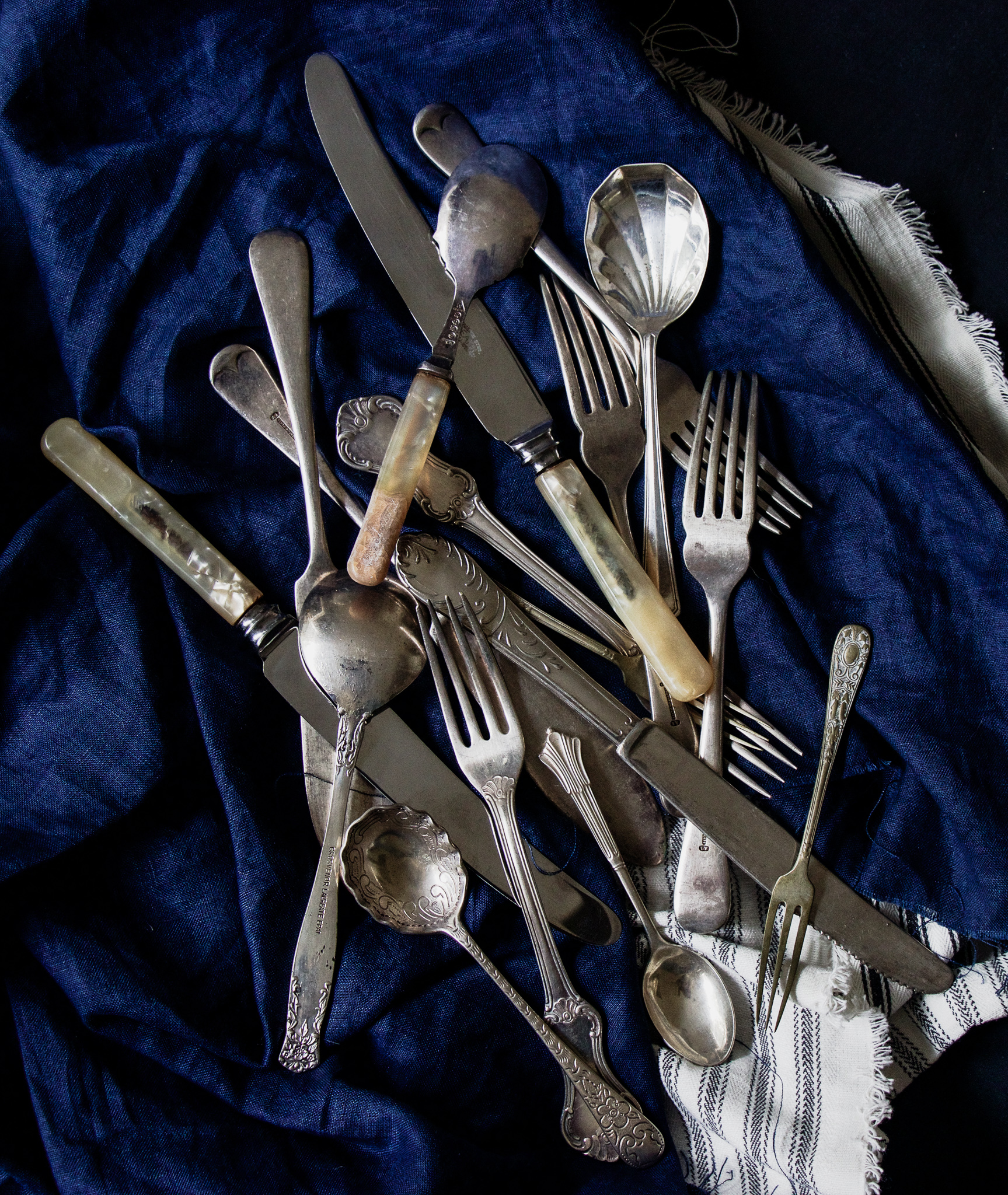 Pieces from my Cutlery Collection - For this image of vintage and antique silverware, I picked pieces with engraved details, varying degrees of age and wear and also combined different shapes and sizes to add texture, tone and points of interest. Layering a dark base with deep blue linen and a contrasting white and blue striped fabric (known as ticking) adds another layer of texture, contrasts with the silverware, and makes the cutlery