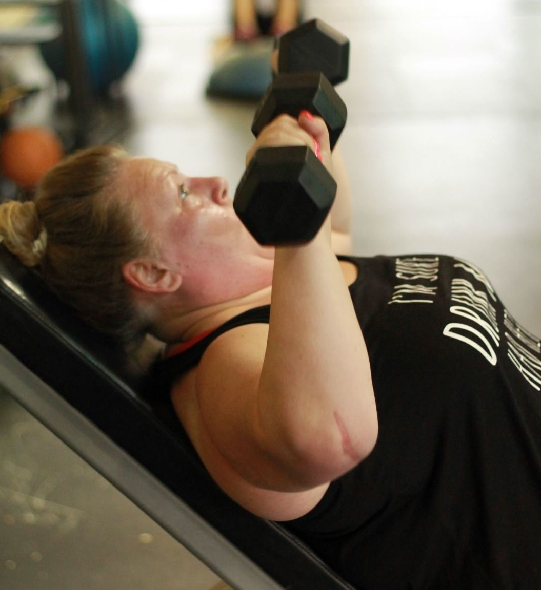 Carol pushes through her last set of incline bench press using dumbbells.