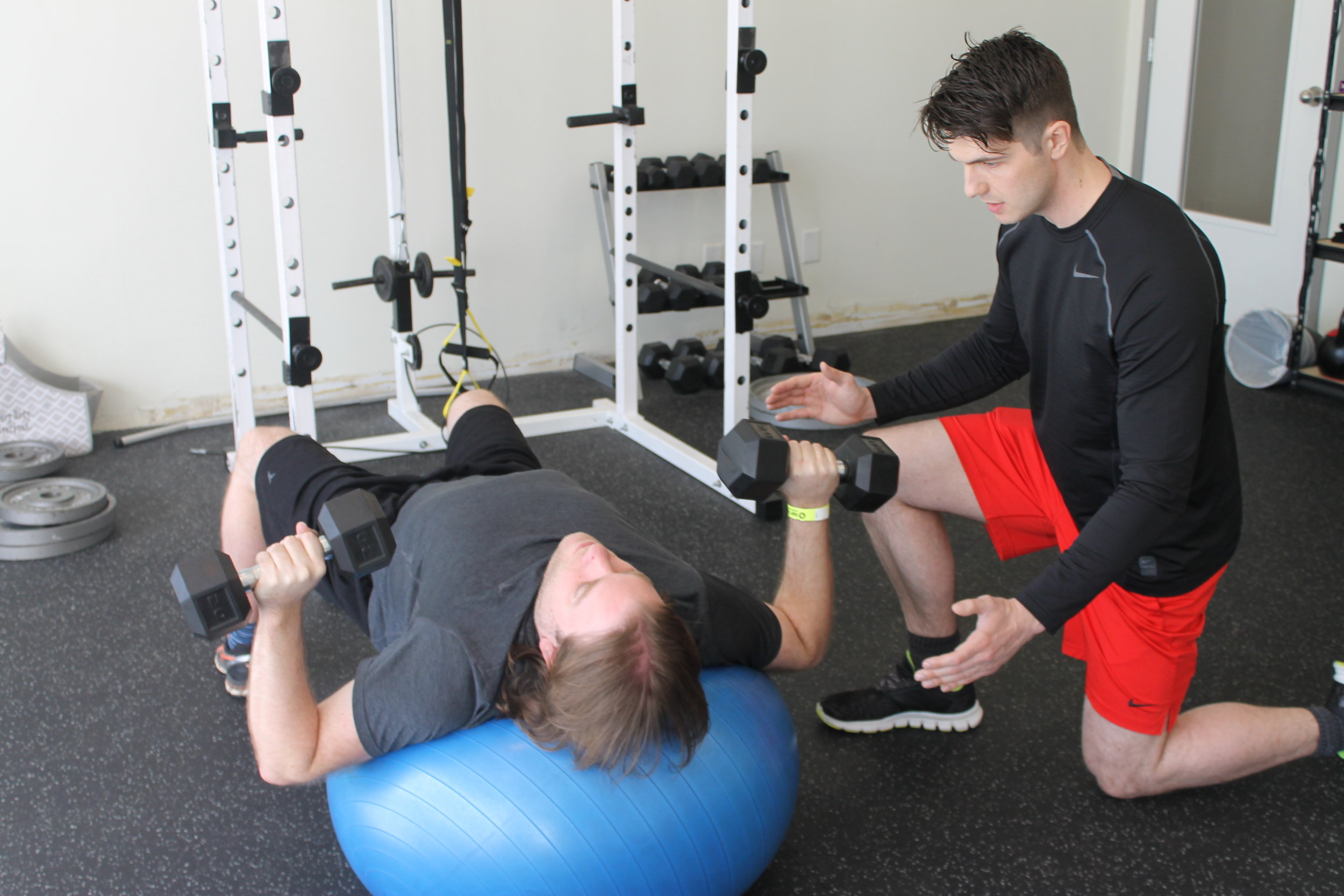 Kyle Lobb supports Jason with his chest press on a stability ball.