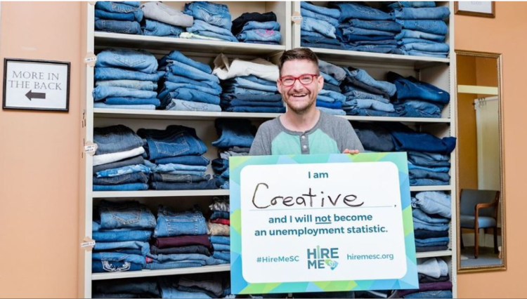 """James standing in front of a jean wall holding a sign that reads, """"I am creative and I will not become an unemployment statistic."""""""