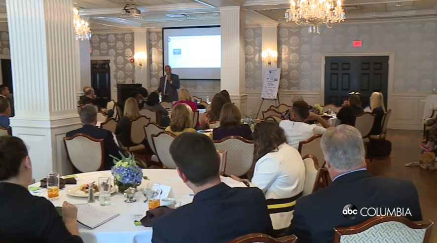 Screencap from the Able SC Columbia piece showing a room full of employers at the Summit watching keynote Nick Schacht speak in front of a PowerPoint.