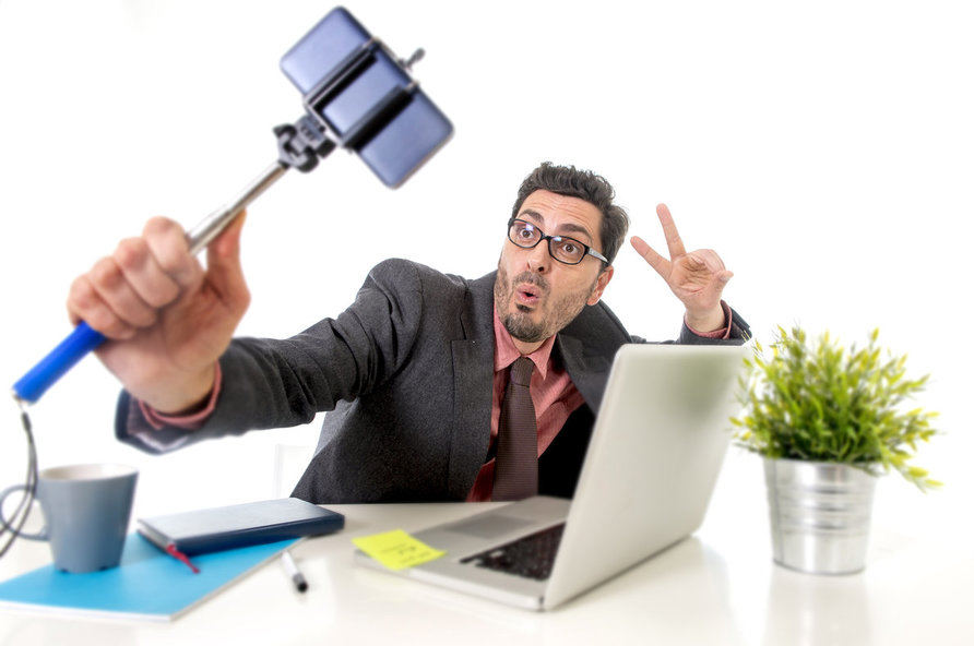 young businessman with glasses in suit and tie working at office desk taking selfie photo with mobile phone camera and stick posing happy and successful isolated on white background