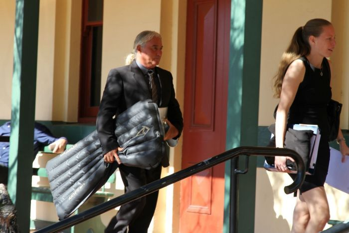"""Thomson entering the Ballina Local Court with his signature """"surf mat."""" Credit: ABC North Coast: Leah White"""