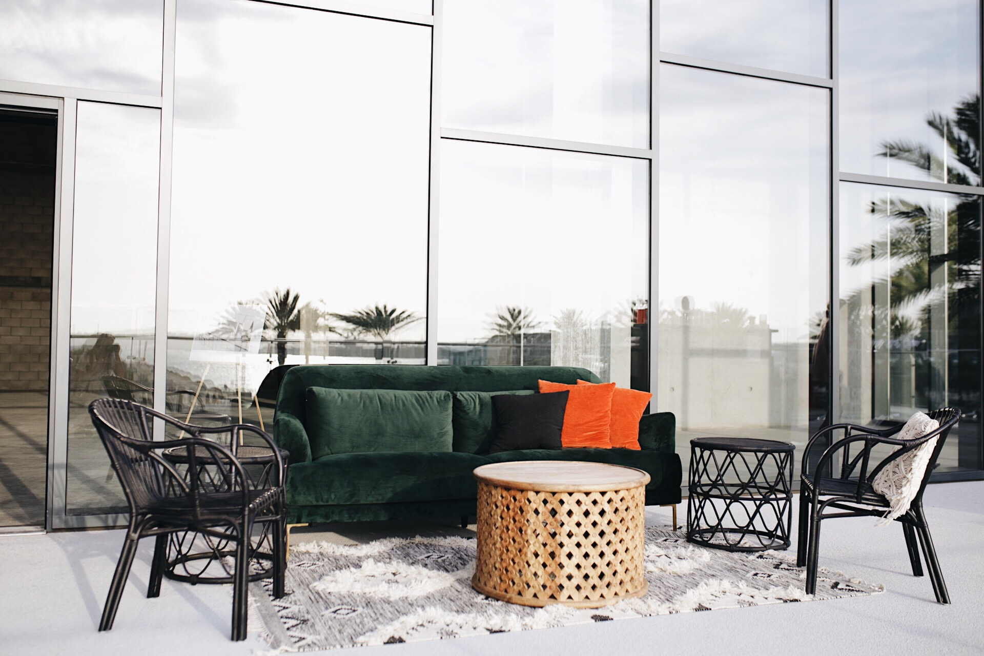 Velvet emerald couch + rattan chairs by  Wonder  complete with sunset views.