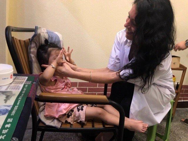 Jenna helping a child