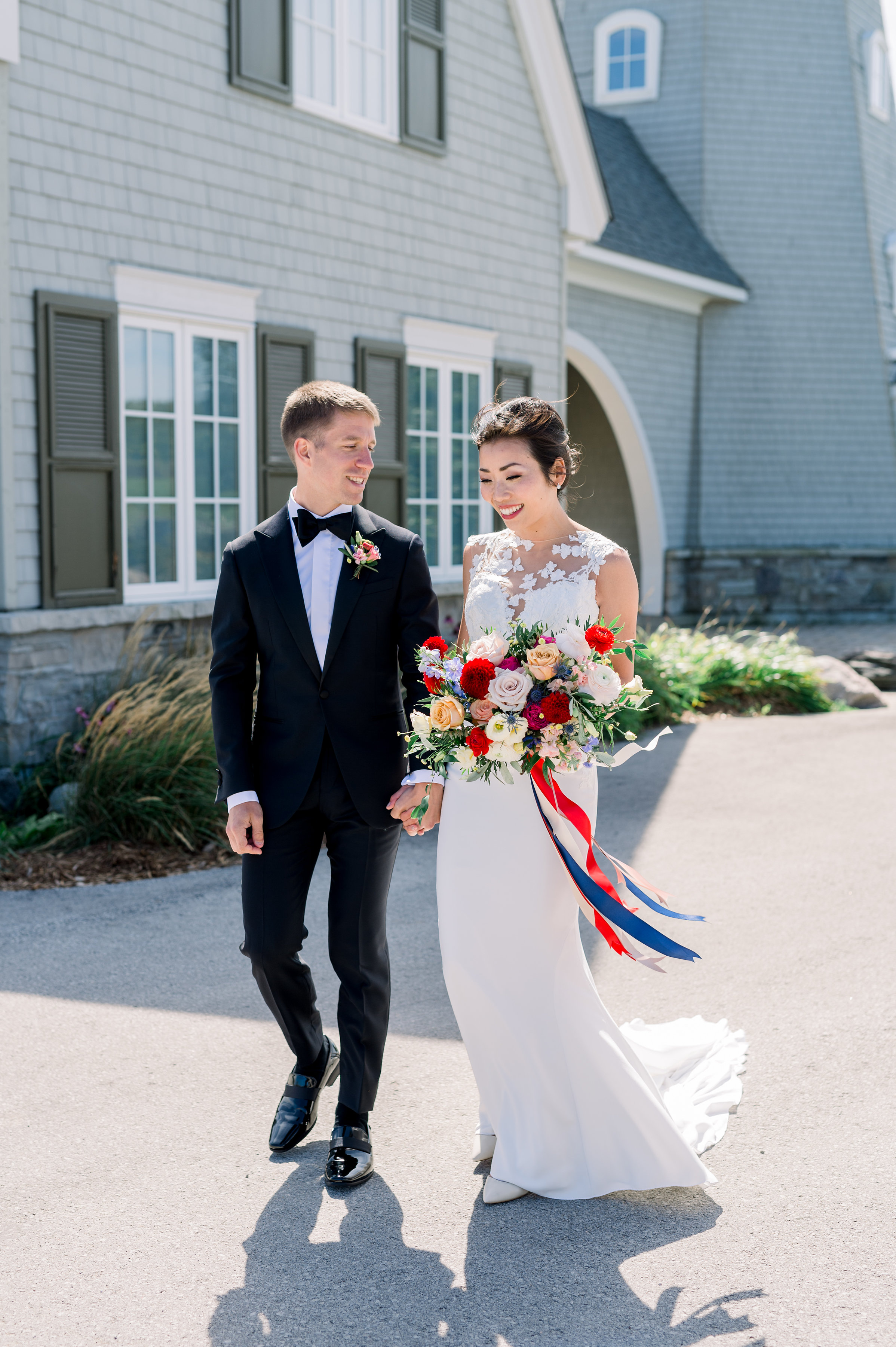 The bride and groom near the lighthouse. Photo courtesy of Whitney Heard. Bride's makeup by Maya Goldenberg, hair by Shanna Layton for Maya Goldenberg, Eco-Beauty Professional. Flowers by Tina from Living Fresh.