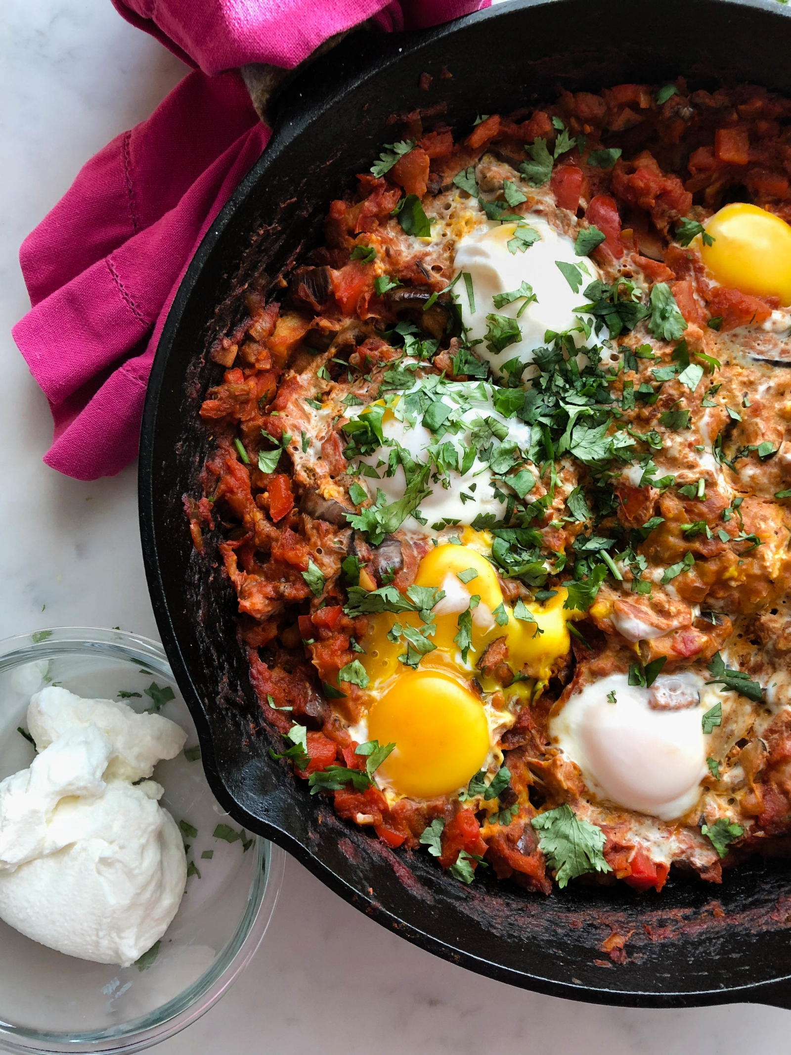 shakshuka - brunch, lunch, or anytime.serves 4 to 61 tablespoon olive oil1 (12-ounce) jar roasted red peppers, drained and coarsely chopped4 garlic cloves, smashed1 to 2 tablespoons harissa1 teaspoon ground cumin1 jar (16 oz.) not just pasta sauceSalt and pepper6 large eggsHandful of minced cilantro, parsley or bothCrumbled feta or sliced oil-cured black olives, for serving (optional)Crusty bread, to serve1. In a large skillet over medium-high heat, heat the olive oil. Add the peppers and cook, undisturbed, until starting to brown, 3 to 5 minutes.2. Add garlic, harissa, and cumin and cook until fragrant, about 30 seconds. Add sauce and season with salt and pepper.3. Reduce heat to medium-low and simmer sauce until slightly thickened, about 5 minutes. Using a small spoon, make a well in the sauce and crack one egg into well. Continue with remaining eggs and season tops of eggs with salt. Spoon a little sauce over the edges of the whites to partially cover them, leaving yolks exposed.4. Cover and cook, simmering very gently and reducing heat if necessary, until whites are set and yolks are still runny, about 10 minutes. Continue basting the egg whites with sauce as they cook.5. Sprinkle with cilantro or parsley and the optional toppings. Serve with crusty bread.
