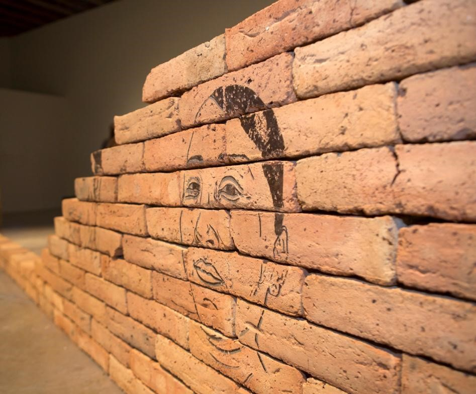 Gabriela Muñoz and M. Jenea Sanchez, Labor, Serigraph on bricks made with Mexican soil, 36 x 264 x 6 inches, 2016. Courtesy of the artists