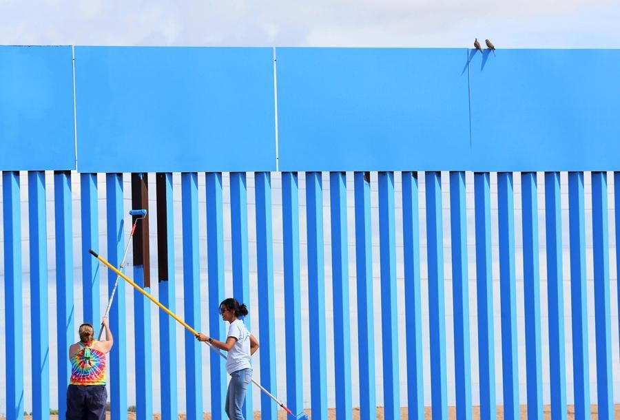 Volunteers Brooke Collins (left) and Ana Lucia Lopez paint the border-fence blue, while two doves sit on top of the wall between the United States and Mexico on April 9, 2016.  Sandy Huffaker / Reuters