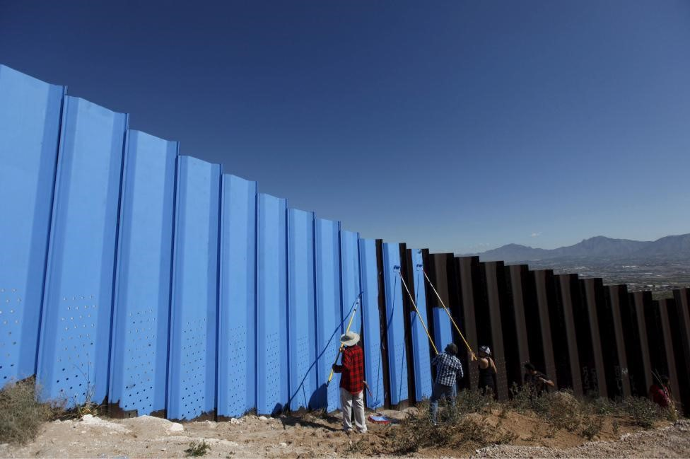 """Artist Ana Teresa Fernandez (in black) and members of cultural organization """"Border/Arte"""" paint the border fence to give it the illusion of transparency in Ciudad Juarez, Mexico. REUTERS/Jose Luis Gonzalez"""
