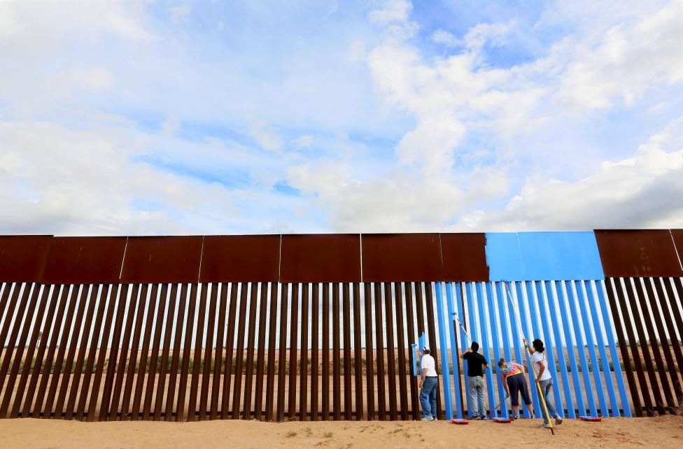 EUTERS/Sandy HuffakerVolunteers paint the border fence in Mexicali, Mexico. R