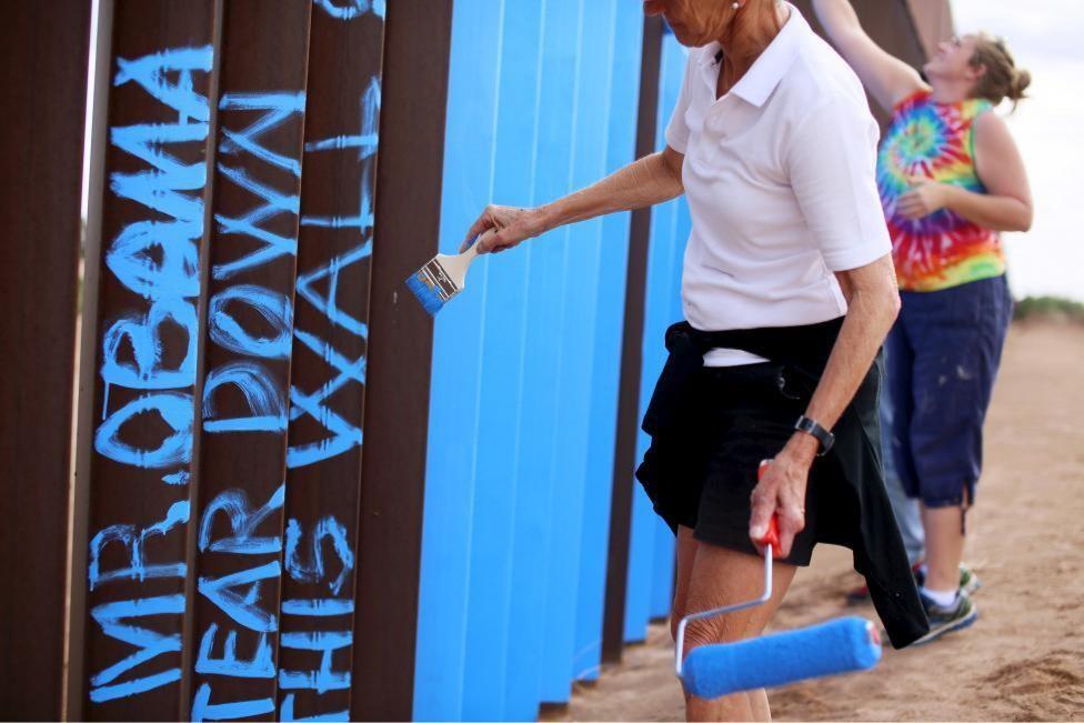 "Artist Ana Teresa Fernandez (in black) and members of cultural organization ""Border/Arte"" paint the border fence in Ciudad Juarez, Mexico. REUTERS/Jose Luis Gonzale"