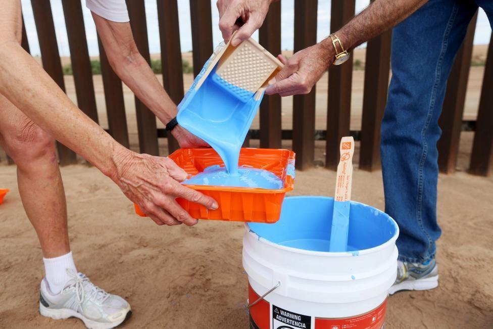 Genaro Fernandez (L) and Dan Watman prepare to paint the border fence in Mexicali, Mexico. REUTERS/Sandy Huffaker