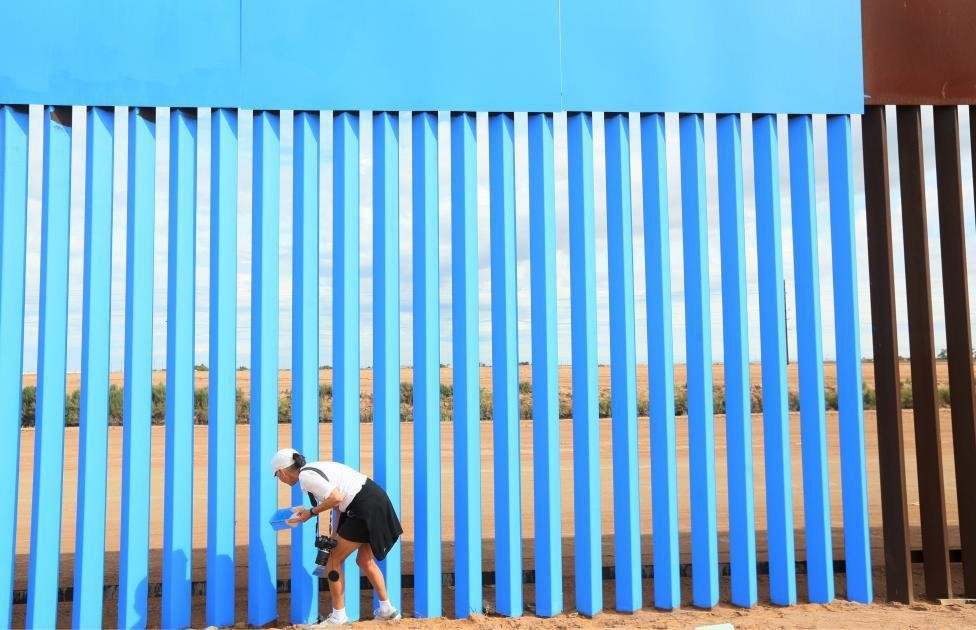 Artist Maria Teresa Fernandez paints the border fence between the United States and Mexico to give it the illusion of transparency. REUTERS/Sandy Huffaker