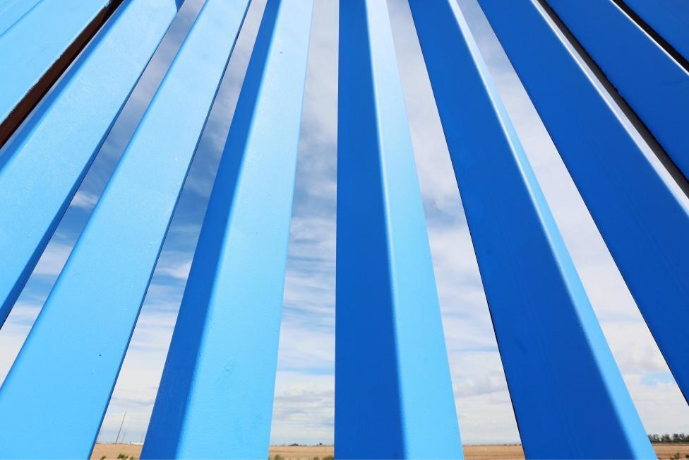 The border fence is seen after volunteers painted it Sky Blue. REUTERS/Sandy Huffaker