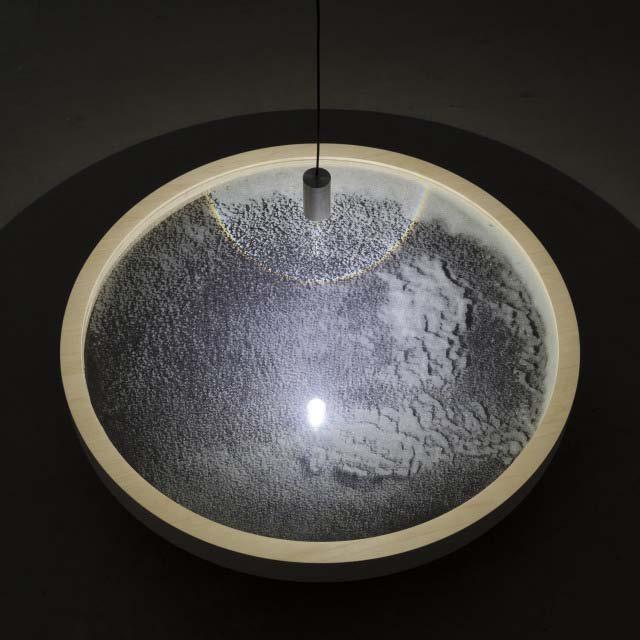 "Chris Fraser, ""SCRY"" (2013), Glass Microspheres, Plate Glass, Maple Plywood, LED Pendant,    25 3/4″ Diameter x 6″"