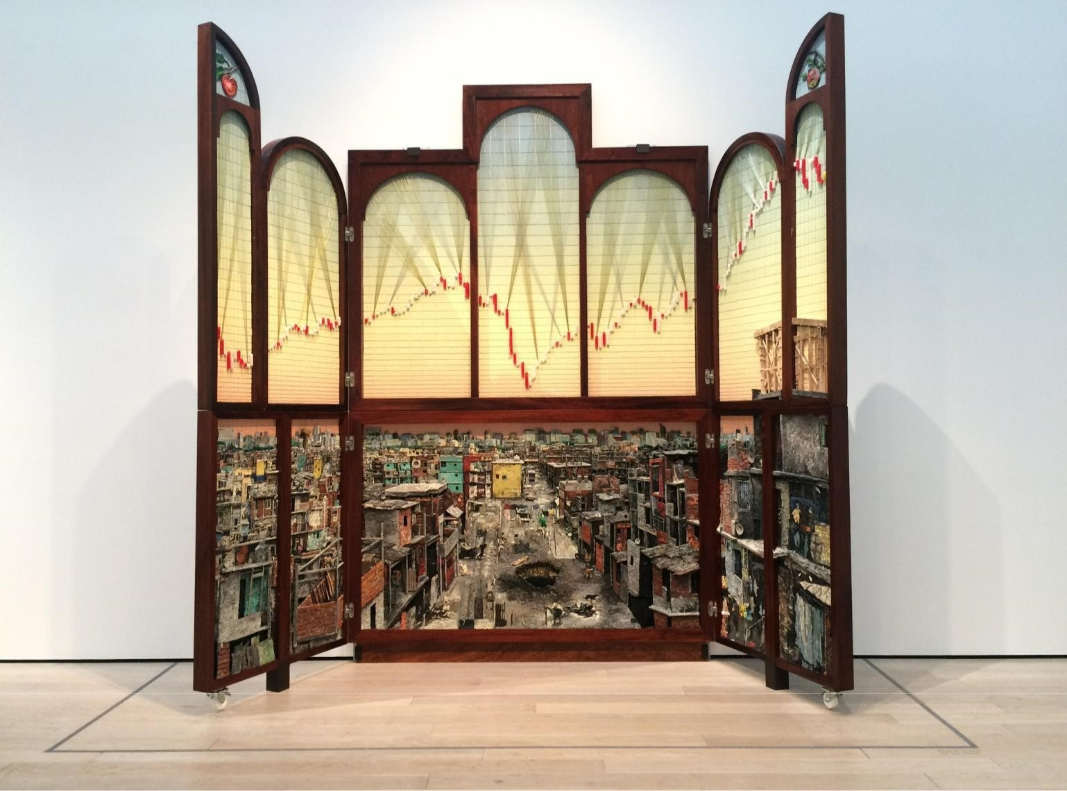 """""""Políptico de Buenos Aires"""" (2014/2016), by the collective Mondongo, shows the disparities of wealth in the Argentine capital. (Carolina A. Miranda / Los Angeles Times)  The exhibition, as Ramirez observes, is not a strict chronological survey of important works by important artists. Instead, it functions more as """"a constellation"""" — """"putting works in dialogue with each other across generations and countries"""" in ways that connect on the level of ideas or materials.  """"We wanted to see what work talked to other work,"""" Noriega adds. """"We saw work talking to work from other countries — even if they might be 50 years apart.""""  A pair of wall-hangings by Raphael Montañez Ortiz, a U.S. artist of mixed Caribbean and Mexican heritage who made some of his key works in the 1960s, for example, hang adjacent to an installation by Colombian artist Leyla Cardenas, who has been active for just over a decade. Both pry apart domestic settings to examine their psychological and historical roots.  Ortiz's pieces, which he labels """"Archaeological Finds,"""" consist of dismembered furnishings that he pries apart in violent acts. Cardenas uses elements of old architecture to conduct what amounts to archaeological digs.  Taking slivers of a decaying 19th century house from Bogotá, she's peeled away layers of wallpaper to reveal decorative elements dating back to the early republic. The structure was made of wood and adobe, in the Spanish style, but the wallpaper added after independence is English. It marks a moment in which Colombia was searching for a new identity apart from Spain.  All of this she presents as a 4-inch-wide slice of a room that looks like a laboratory specimen on an architectural scale.  """"From a piece of the room, you can reconstruct not just the room, but the house and the city and the country and what was going on at any given time,"""" she says. """"It fits with the show, which offers a transversal look at the concept of home."""""""