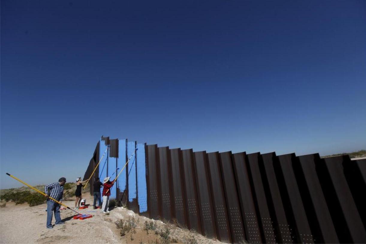 "Artist Ana Teresa Fernandez (in black) and members of cultural organization ""Border/Arte"" paint the border fence in Ciudad Juarez, Mexico. REUTERS/Jose Luis Gonzalez"