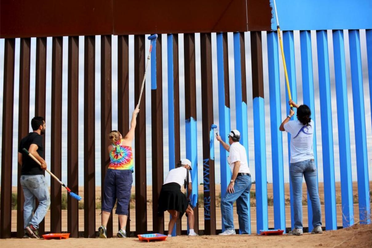 Volunteers Dan Watman, Brooke Collins, Maria Teresa Fernandez, Genaro Fernandez and Ana Lucia Lopez paint the border fence between the United States and Mexico to give it the illusion of transparency.