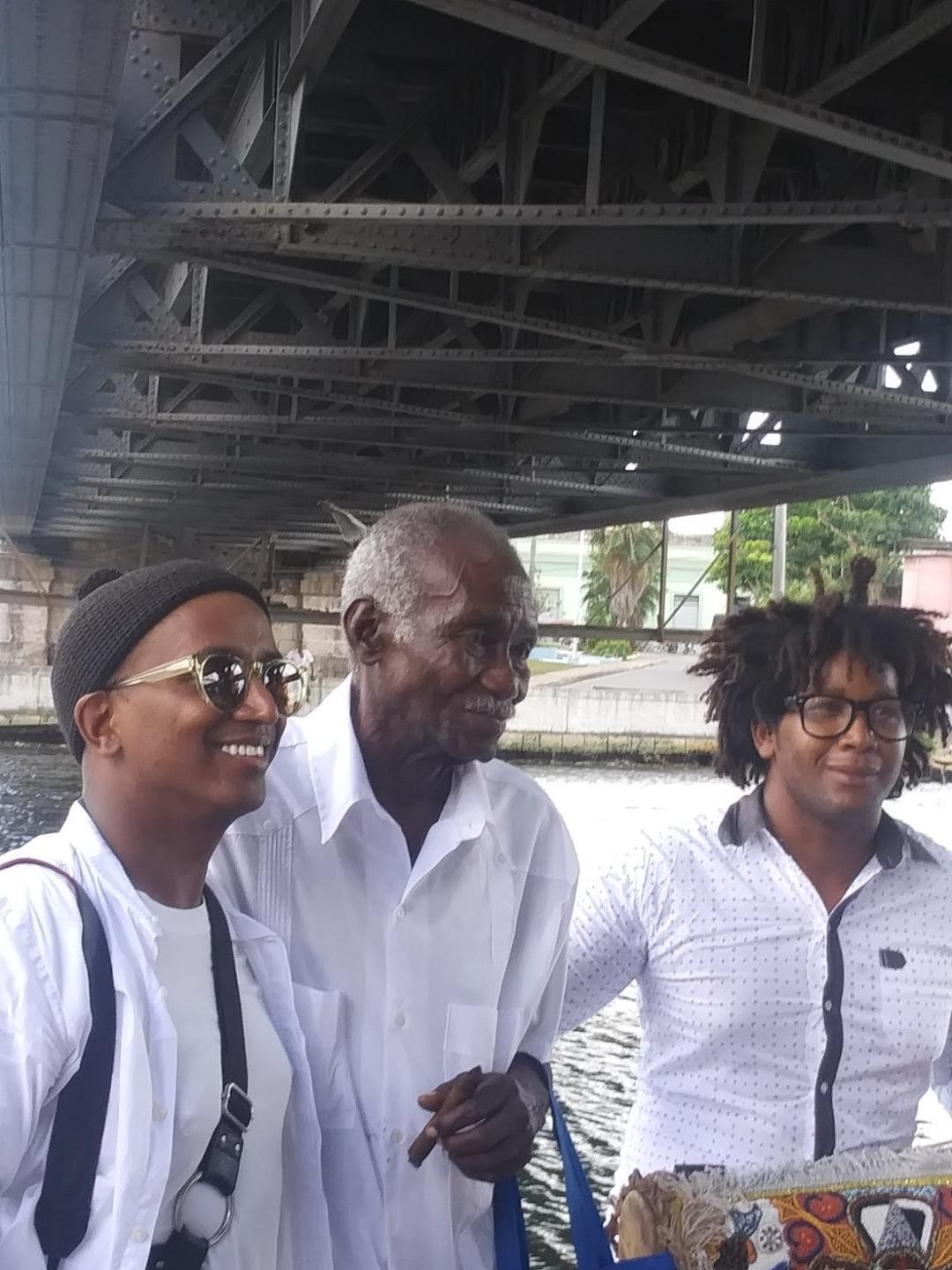 After the performance, artist Dawit L. Petros, left, poses with his mentor on the project, center, and the drummer who performed on the river wall Photo: Cuban Art News