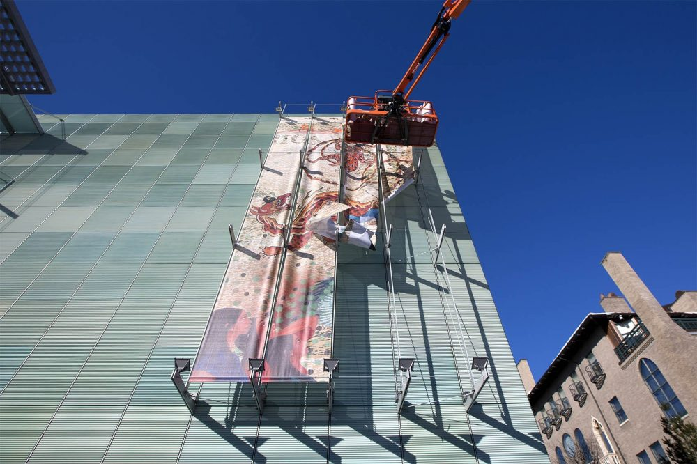 """Contractors work on the installation of """"I Need a Hero."""" (Jesse Costa/WBUR)"""