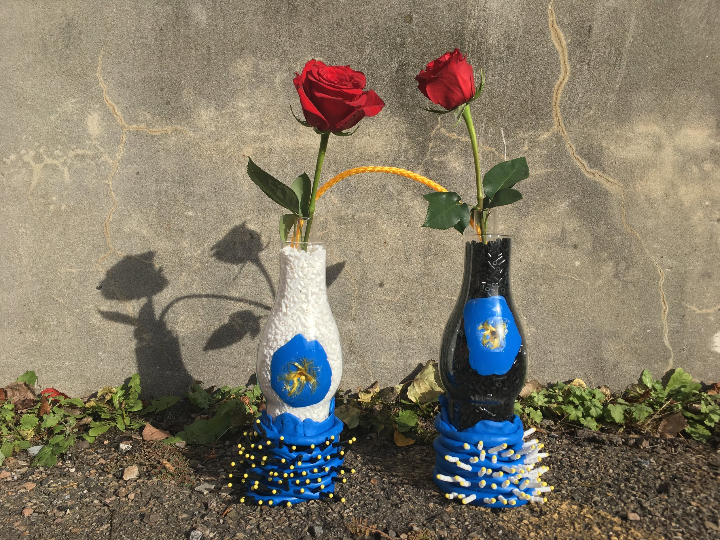 Materials: glass oil lamp chimneys, modeling clay, Perler beads, quilting pins, test tubes, roses, rope.