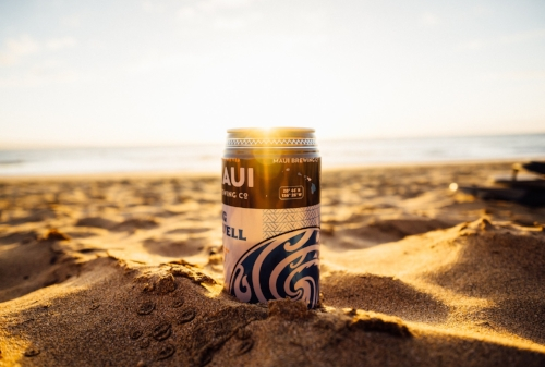 Maui brewing company beer can on the beach in the sand