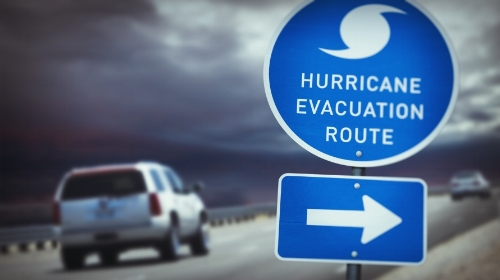 Hurricane Evacuation Route sign with traffic and dark clouds