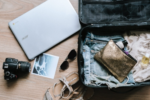 open luggage suitcase with clothes laptop camera sunglasses