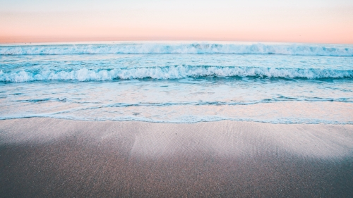 beach and ocean waves at the shore during sunrise
