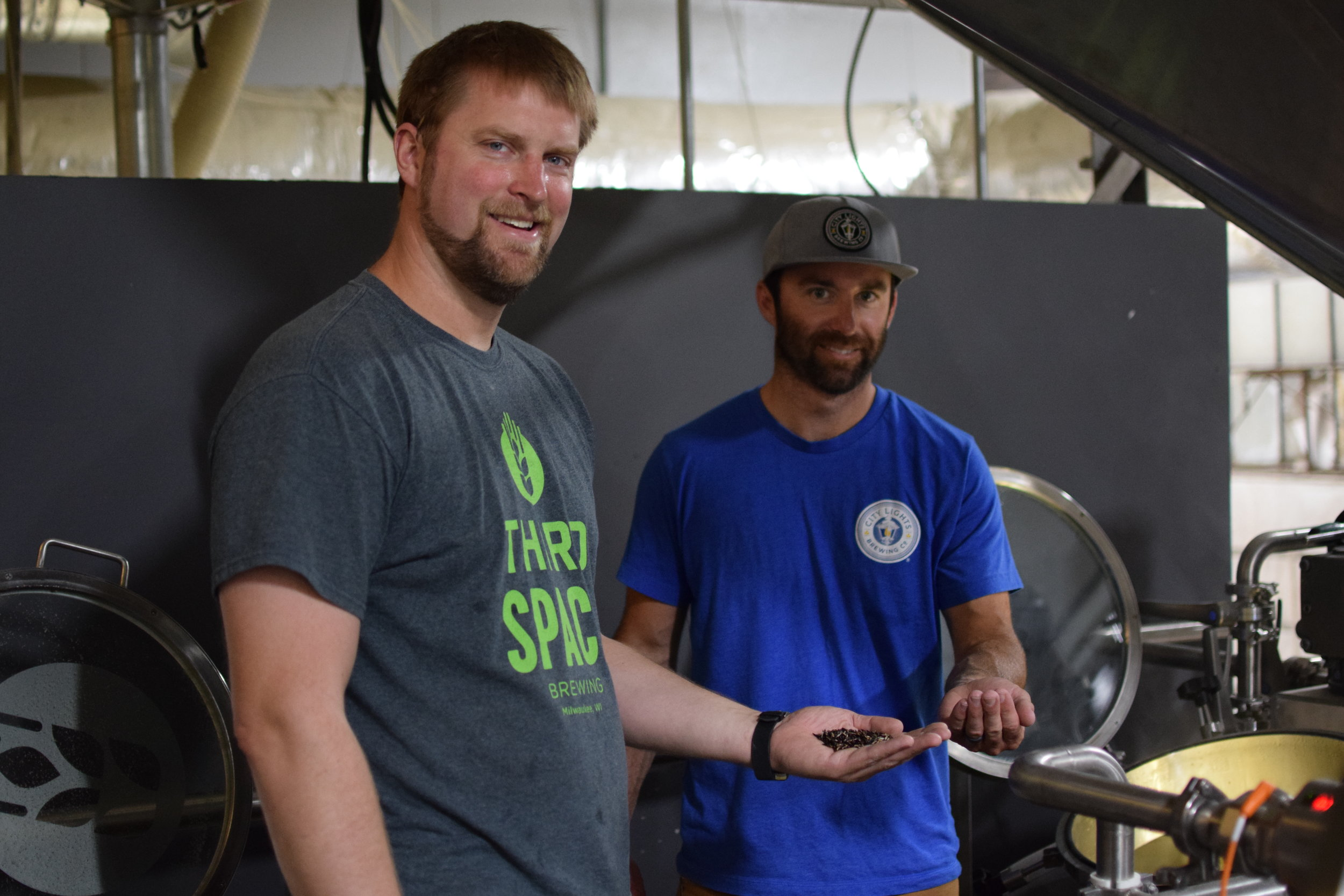 Master brewers, Kevin Wright of Third Space Brewing & Jimmy Gohsman of City Lights Brewing, holding wild rice used in the limited edition beer
