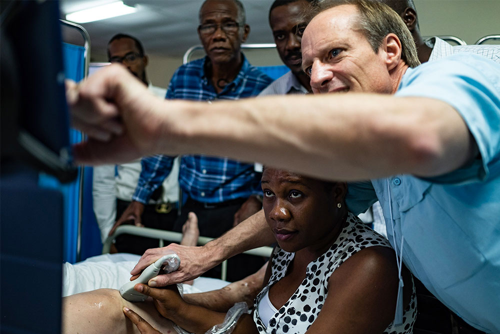 Dr. Cliff Gronseth guiding Dr. Anette Tenvil from Belladère, Haiti, through a simple knee ultrasound while using the mskNAV application, reference software he developed at 7D Imaging | Photo: Jason Houston